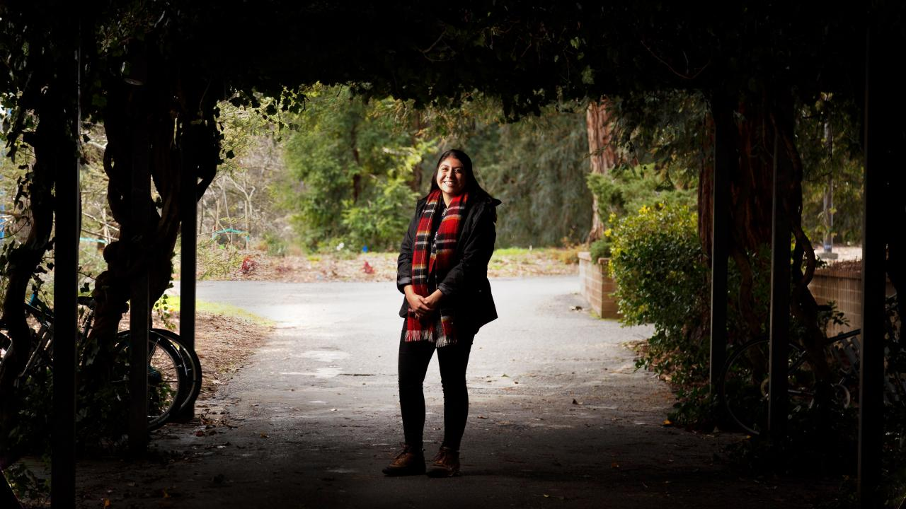 First-gen student, Lucero Morales, standing in the arboretum