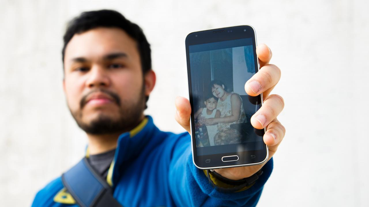 Miguel Flores holding a phone that displays a photo of Miguel with his mom at a younger age