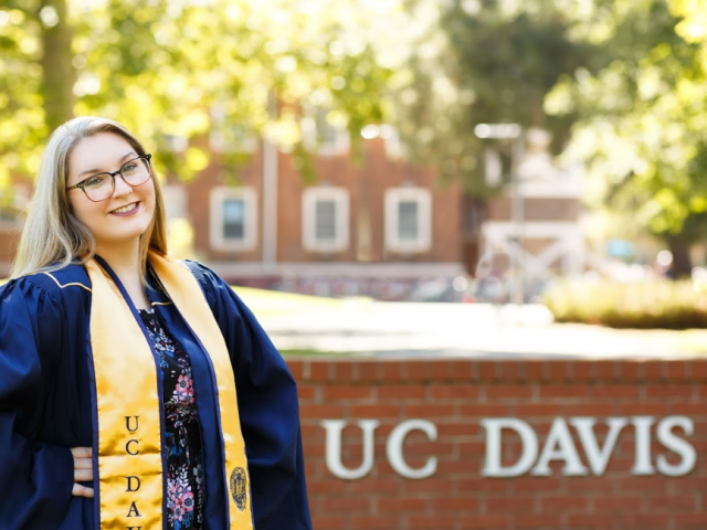 First-generation student, Chelsea Blankenship, smiling in a gold UC Davis stole.