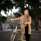 Layla Al Asadi standing with her bike in the middle of the UC Davis bike lane.