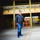 First Generation College Student Dave Ivan Cruz stands in front of the Student Community Center (SCC).