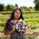 First-generation student, Yilda Korepela standing in the UC Davis student farm holding her graduation cap that features photos from her family and childhood.